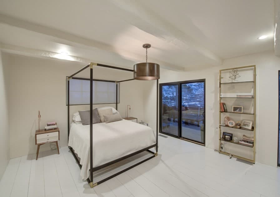 A modish Scandinavian-Style master bedroom featuring white hardwood floors and stylish side tables along with shelving on the side.