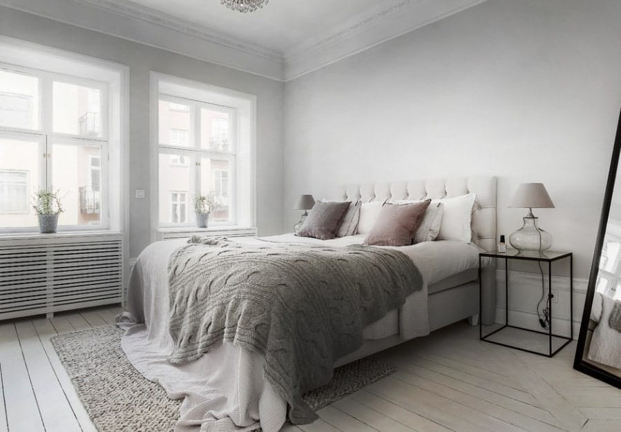 A stylish Scandinavian-Style master bedroom boasting gray walls and hardwood flooring that matches the rug on top of it.