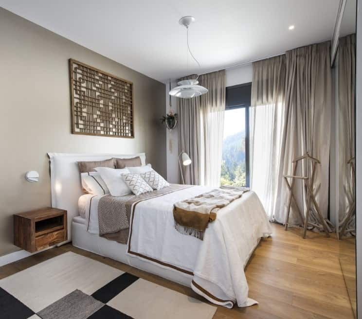 Small Scandinavian-Style master bedroom with classy window curtains and a stylish rug on top of the hardwood flooring.
