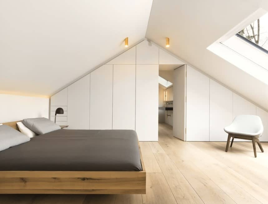 This Scandinavian-Style master bedroom features white walls and vaulted ceiling with a skylight.