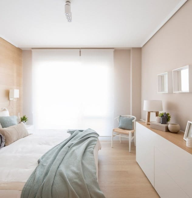 Small Scandinavian-Style master bedroom with lovely window curtains and beige walls that fit perfectly well with the room's style.