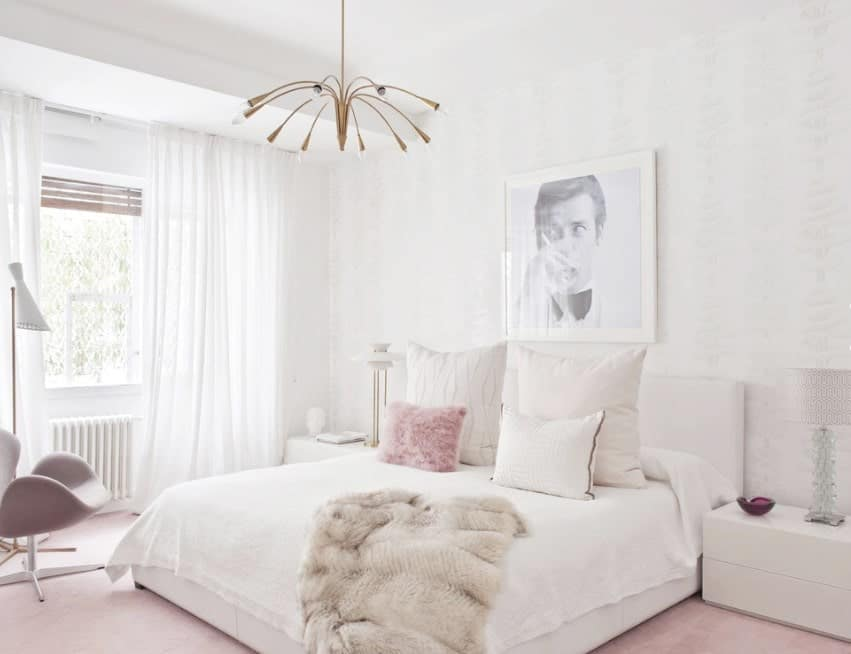 A chic Scandinavian-Style master bedroom with pink carpet flooring and white walls that match the bed and side tables perfectly. The white window curtains look very lovely as well.