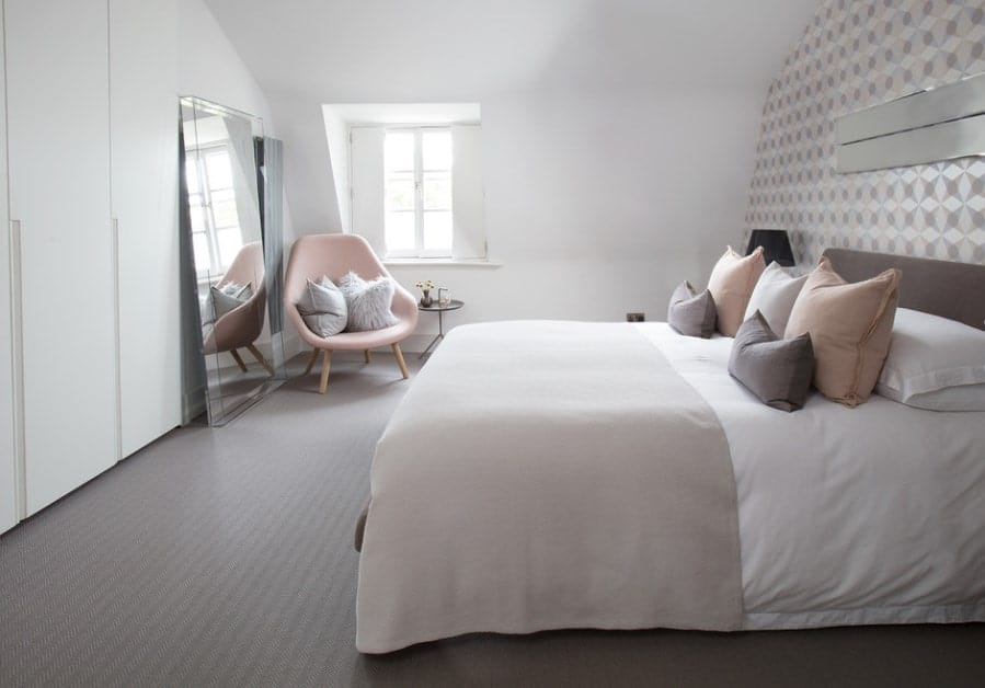 Classy Scandinavian-Style master bedroom featuring gray rug flooring and a stylish wall. There's a cute pink chair on the corner near the window.