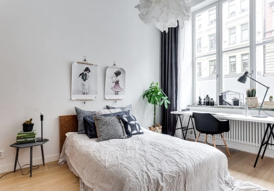 White Scandinavian-Style master bedroom featuring a study desk near the window with elegant black and white window curtains.