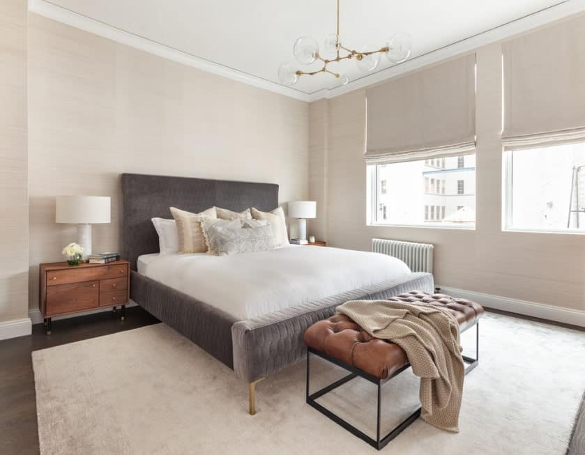 A modish Scandinavian-Style master bedroom with a luxurious bed and a classy rug covering the hardwood flooring. The room is surrounded by charming beige walls.