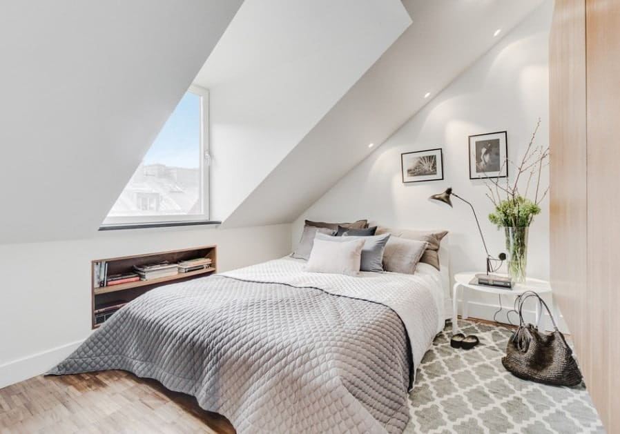 Small Scandinavian-Style master bedroom featuring a shed ceiling and stylish hardwood flooring topped by a rug.