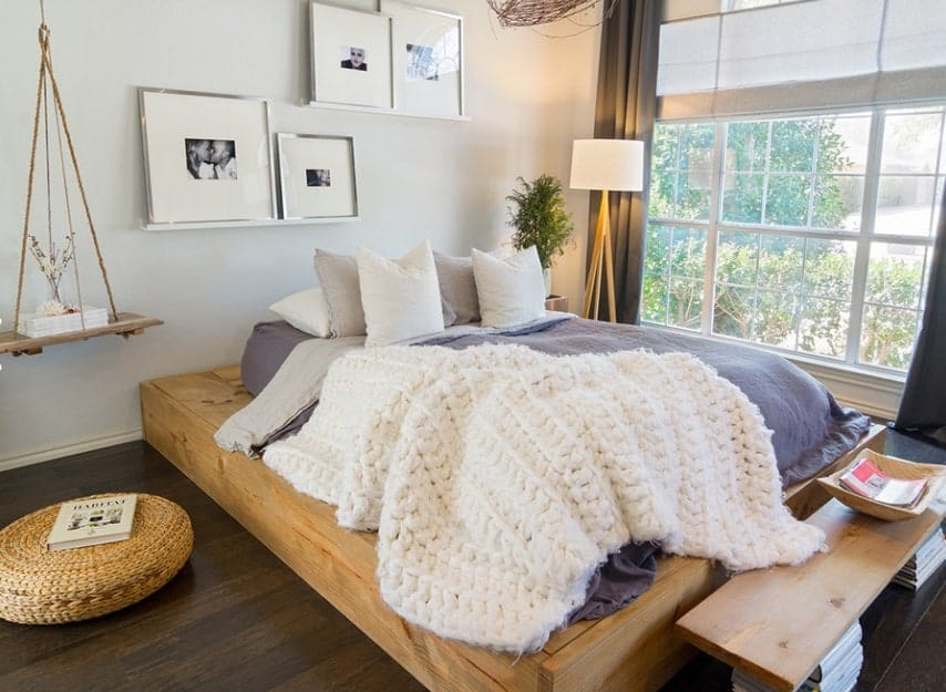 This Scandinavian-Style master bedroom features a stylish bed set on the hardwood flooring. There's a large window beside the bed with stylish curtains.