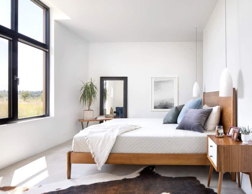A classy Scandinavian-Style master bedroom featuring white walls and modish pendant lights. The rug covering the white flooring looks very stylish.