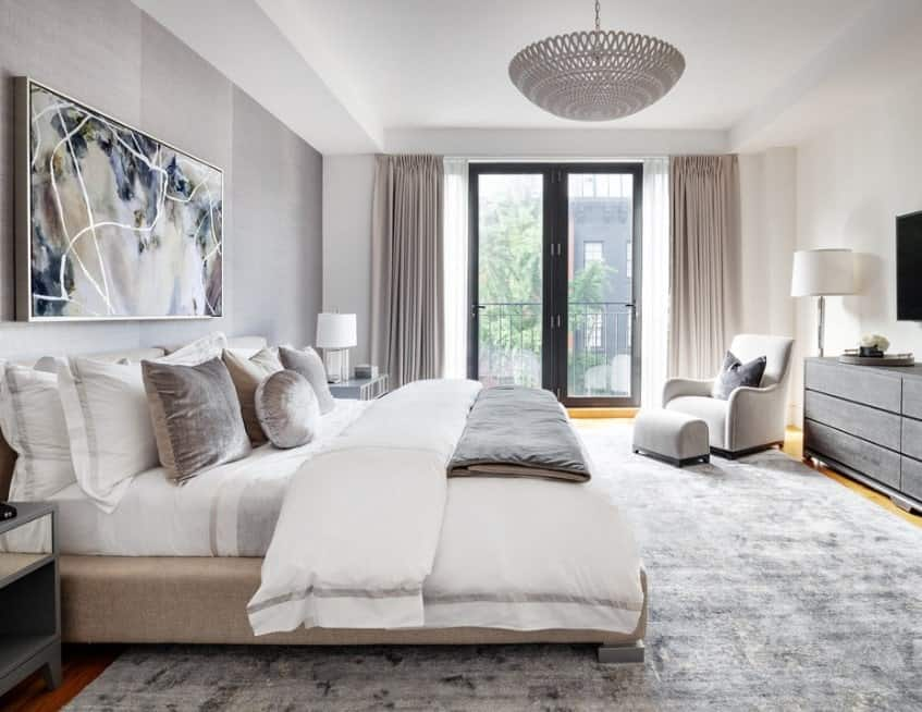 Stylish Scandinavian-Style master bedroom featuring a massive gray rug. The wall decor adds charm to the area.