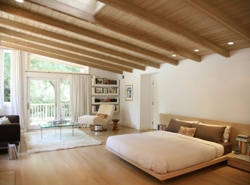 Large Scandinavian-Style master bedroom featuring a glamorous wooden ceiling with beams matching the hardwood flooring. The bed looks very stylish and romantic. There's a reading nook on the side as well.
