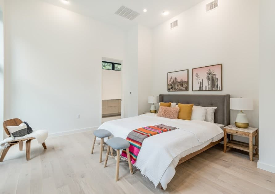 Large Scandinavian-Style master bedroom with its own bathroom. The room is surrounded by white walls and ceiling along with hardwood flooring.
