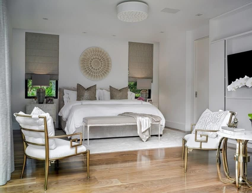 A glamorous Scandinavian-Style master bedroom with a luxurious bed set on the classy white rug covering the hardwood flooring.