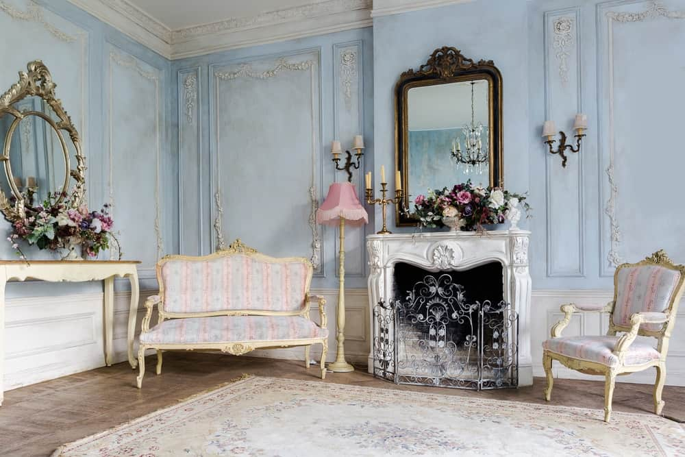 This shabby-chic living room has elegant beige sofa and armchair that goes well with its pink and light blue patterned cushions. These are complemented by the light blue walls with subtle intricate details on its finish paired with white low wainscoting a white-mantle fireplace.