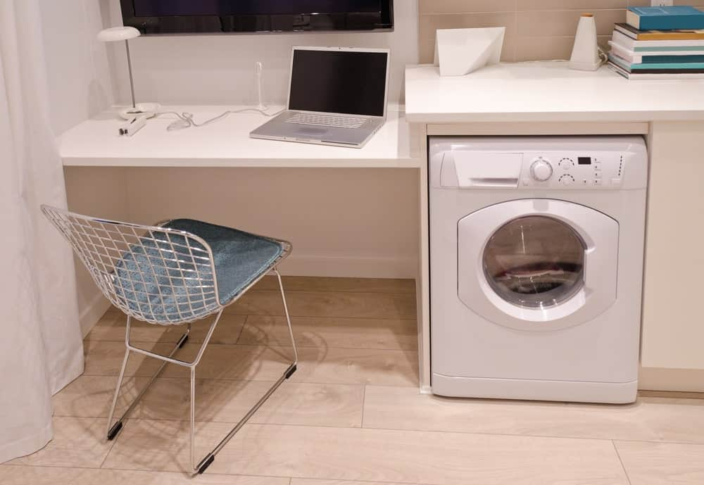 This laundry room has a small study desk beside the washer set on the hardwood flooring. The white counter matches the white built-in desk.