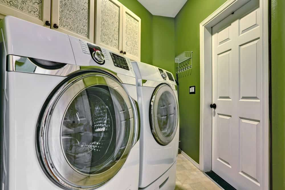 Small laundry room featuring green walls and small tiles flooring. The room has a large washer and dryer combo.