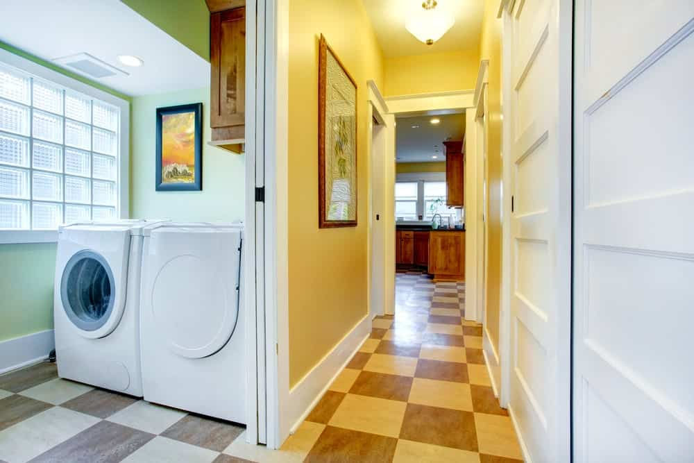 A laundry room featuring checker tiles flooring and green walls surrounding the washer and dryer combo.