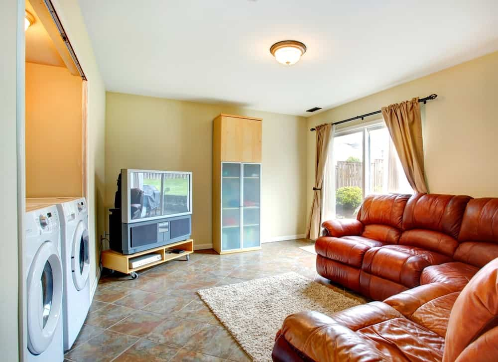 This laundry room boasts an elegant brown set of seats with a TV on the corner.