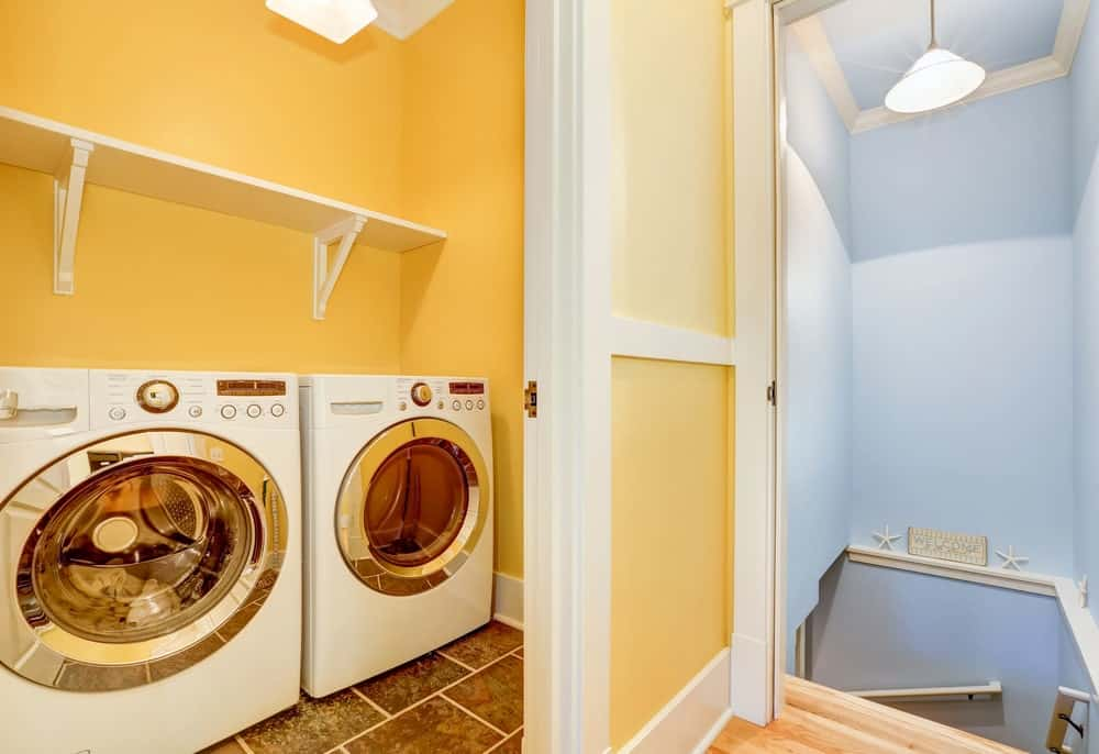 A walk-in laundry room with a washer and dryer combo. The area features tiles flooring with yellow walls.