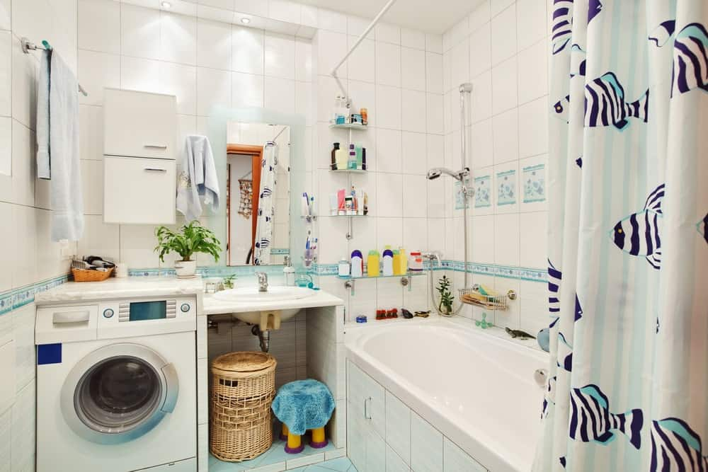 A bathroom and laundry combo featuring a washer beside the sink, surrounded by white tiles walls.