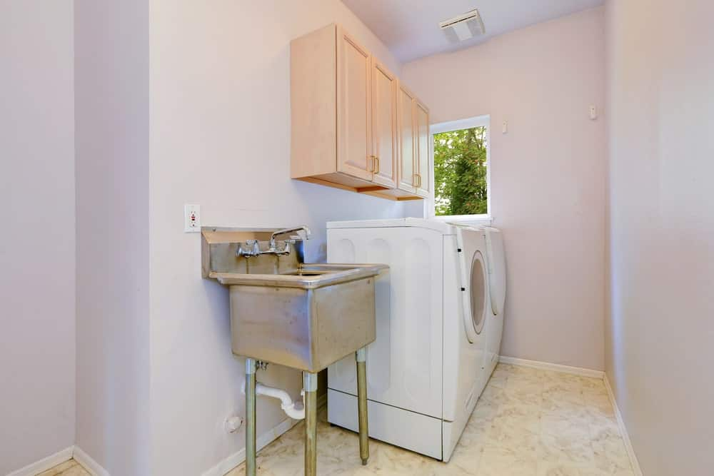 A laundry room surrounded by pretty white walls and marble tiles flooring. The cabinetry looks so gorgeous as well.