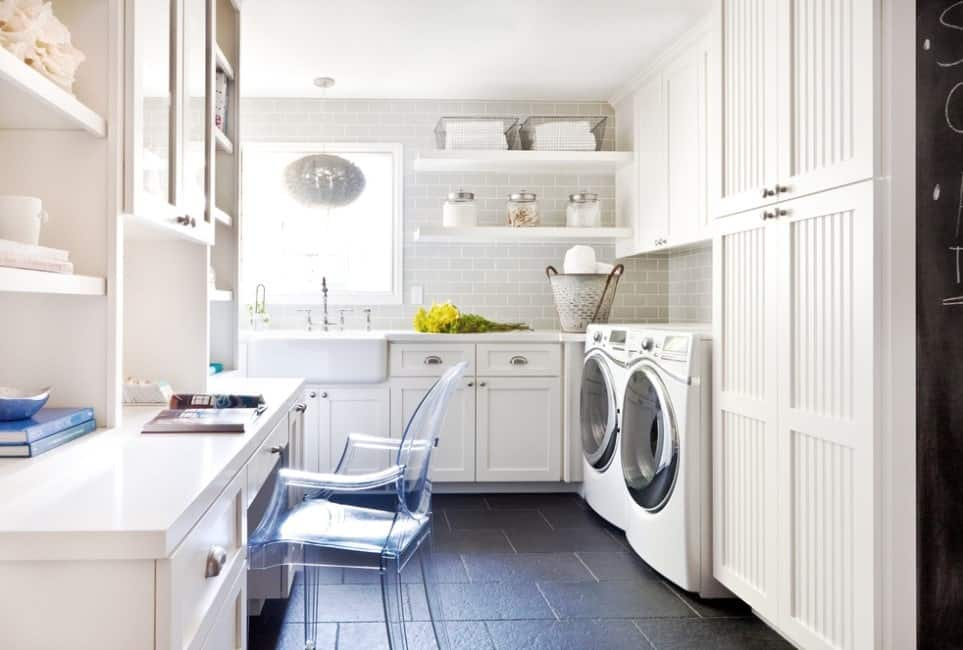 Large laundry room featuring a counter and cabinetry along with multiple shelving. There's also a desk as well.