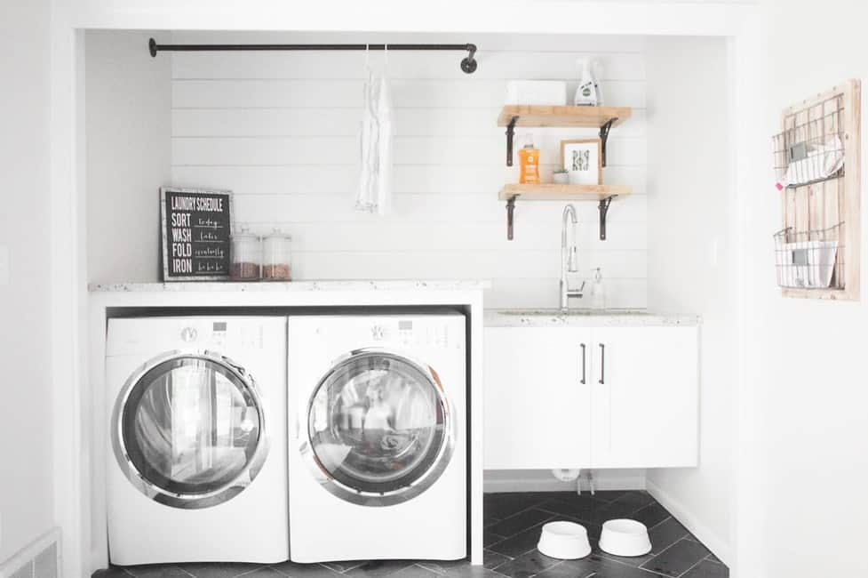 A white laundry area featuring classy marble countertops on the counters. The white walls look perfect together with the black tiles flooring.