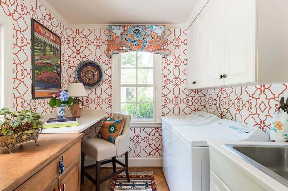 The red and white walls of this laundry room look absolutely stunning. There's a small study desk with a cozy chair as well.