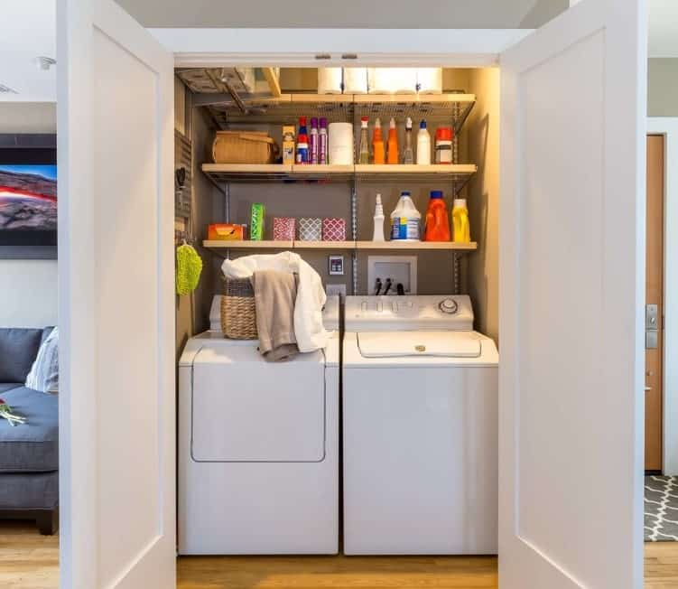 A closet-type laundry featuring white washer and dryer matching the white doors.