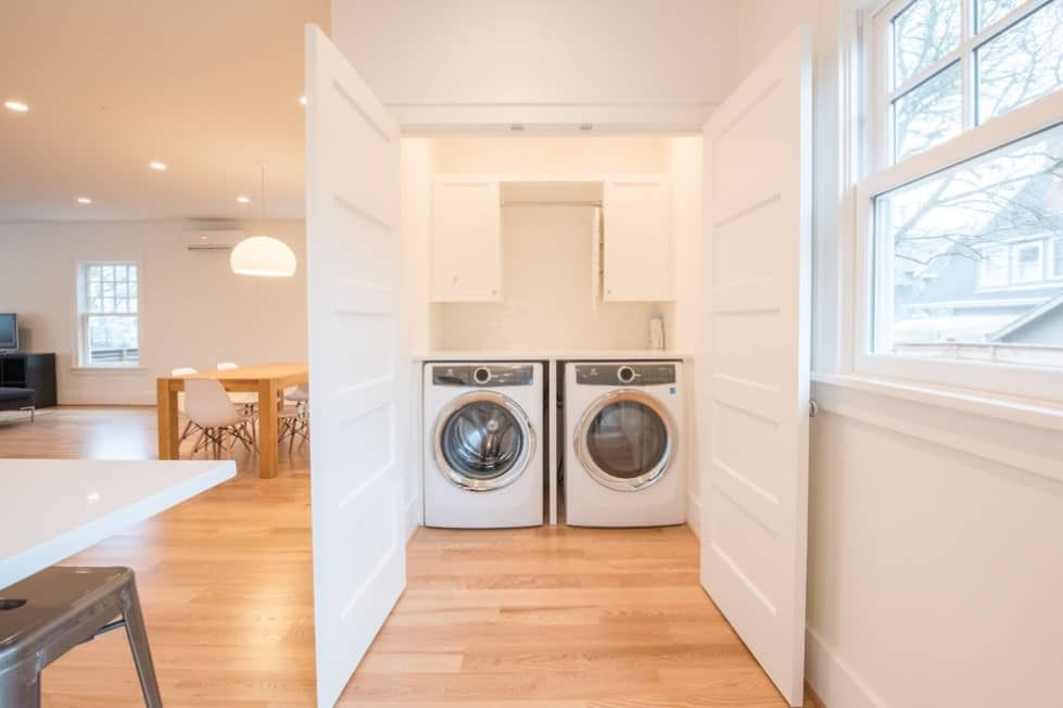 White and large closet-type laundry with white walls and white doors.