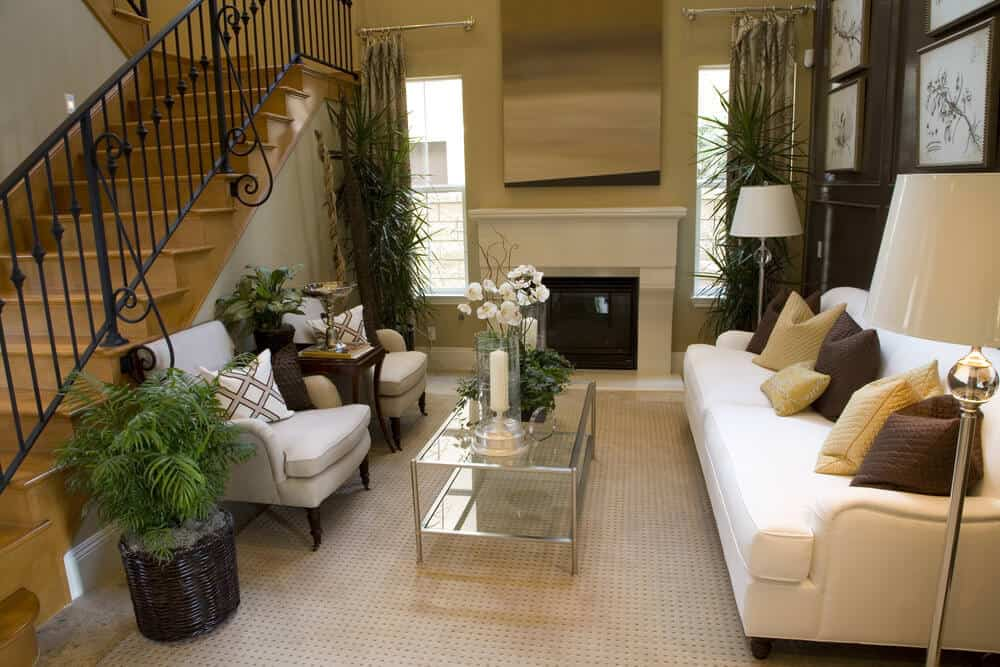 This is small living room that is placed right beside the staircase that has intricate wrought iron railings. The small area is covered with a light gray area rug that goes well with the modern glass coffee table. This sits in the middle of the beige sofa and the two light gray cushioned armchairs.