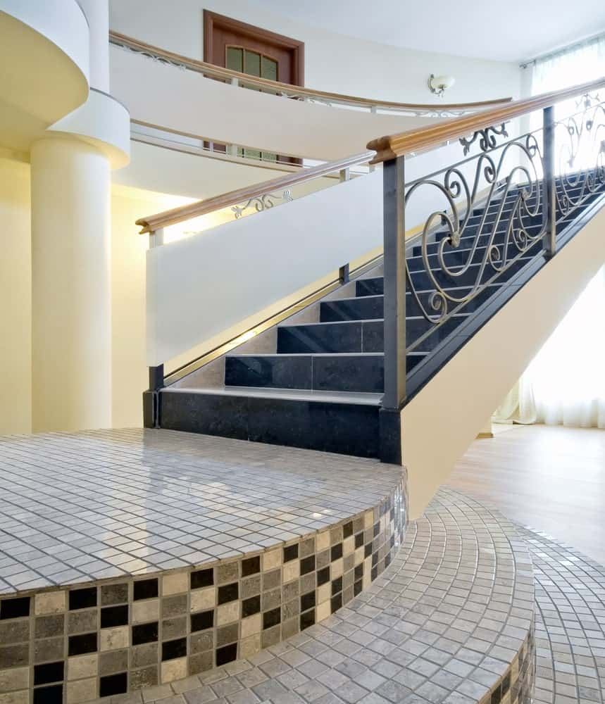 A staircase with three-layer tint tiles landing. The staircase itself features black tiles flooring and has classy railings.