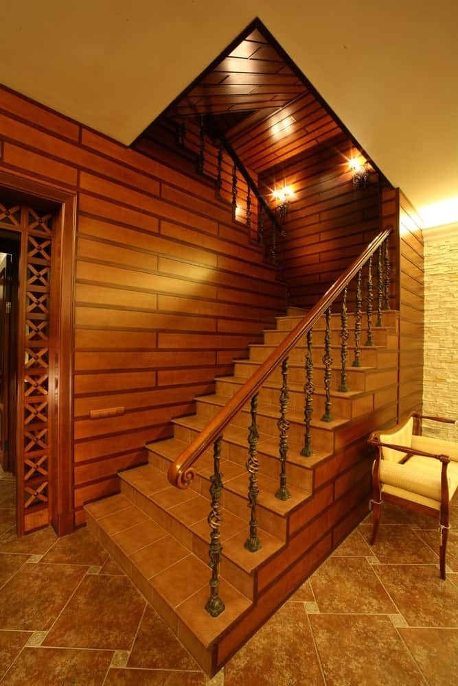 A home's entry with a rustic-style staircase with tiles flooring and attractive walls, lighted by charming wall lights.