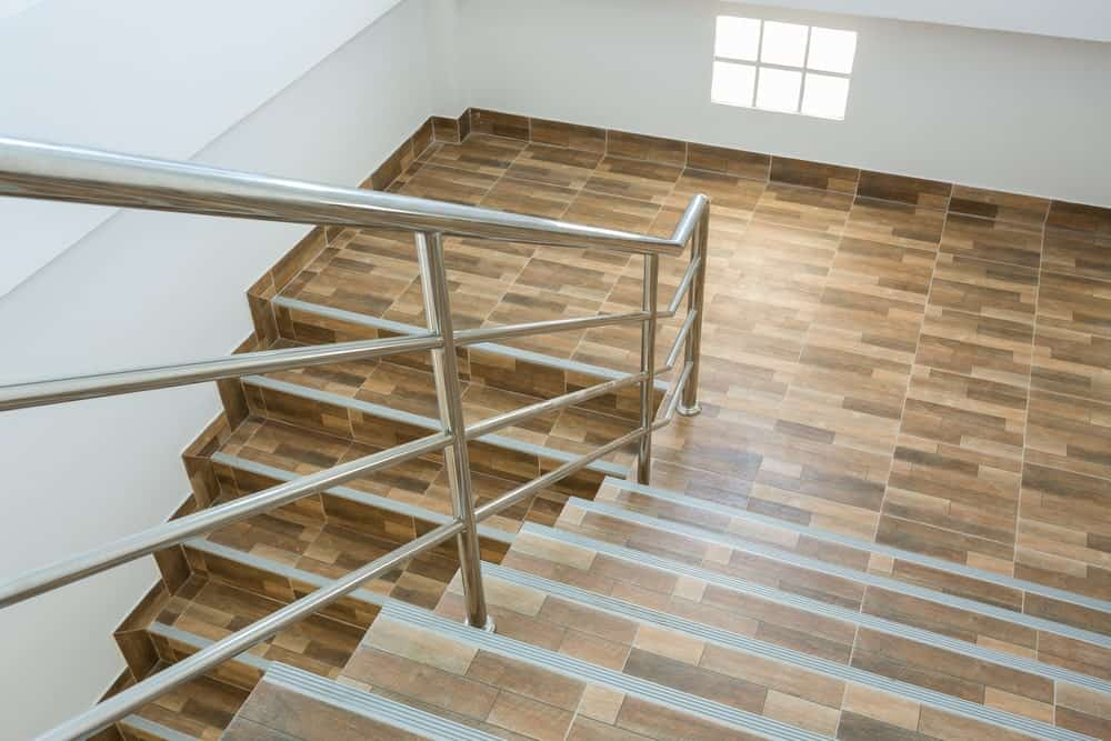 A large staircase with enchanting tiles flooring and stainless steel railings surrounded by white walls.