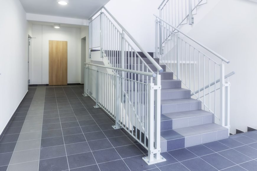 A staircase with blue tiles flooring and white railings matching the white walls.