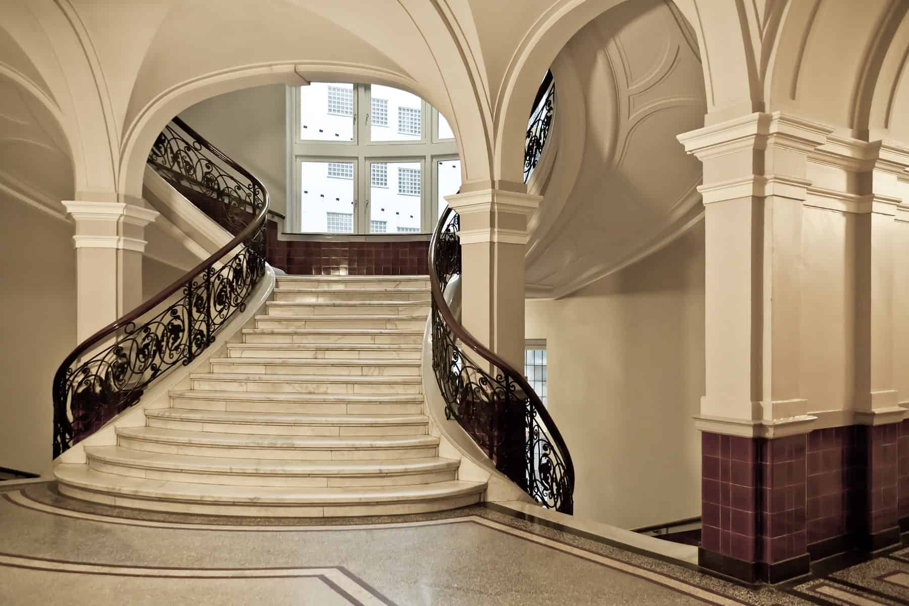 A grand foyer featuring a split staircase with classy marble tiles flooring and elegant railings.