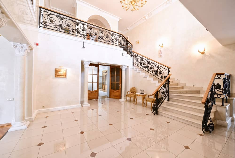 A grand foyer featuring classy tiles flooring, white walls and a glamorous staircase with elegant black railings and is lighted by wall lights.