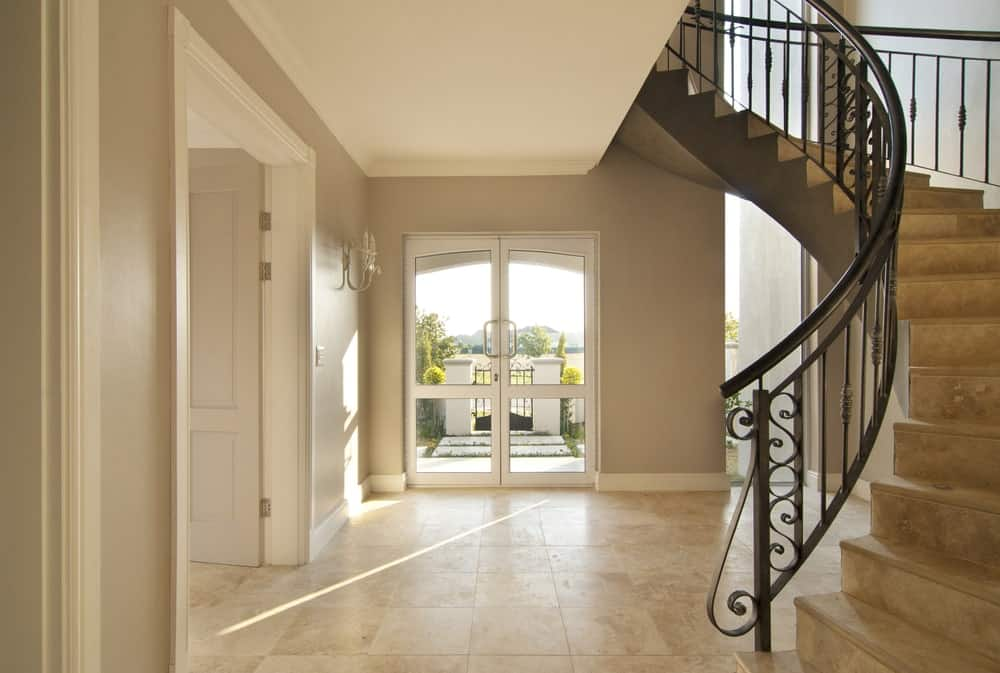 A home entry with a circular staircase featuring beige tiles flooring that looks so dashing.