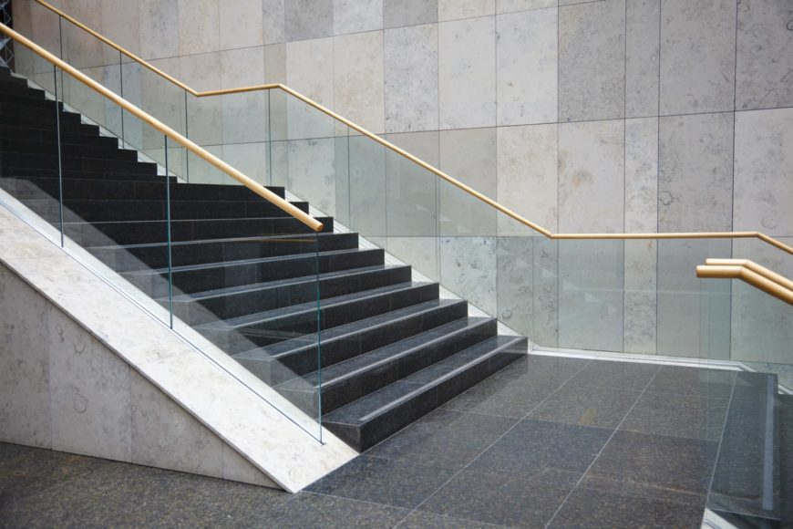 A large straight staircase featuring black tiles flooring and glass railings.