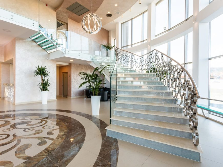 A grand foyer with a marvelous staircase featuring tiles floors and very attractive railings.