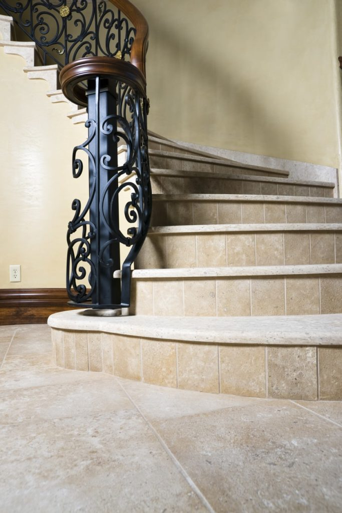 A close up look at this curved staircase's tiles flooring and iron railings.