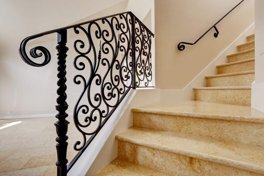 A close up look at this staircase's gorgeous tiles flooring and charming black railings.