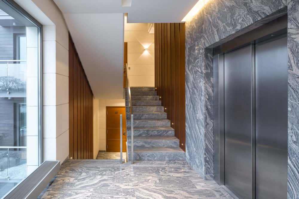 A modern building with stunning flooring and staircase with iron railings and stylish walls.
