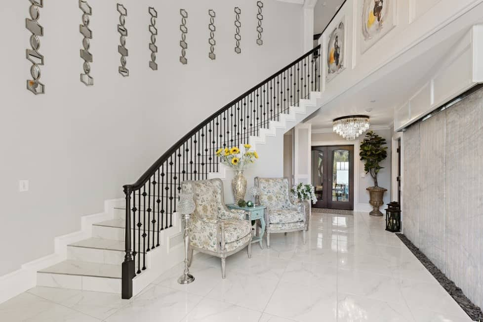 A home entry featuring classy marble tiles flooring, a pair of elegant chairs and a staircase with espresso railings.