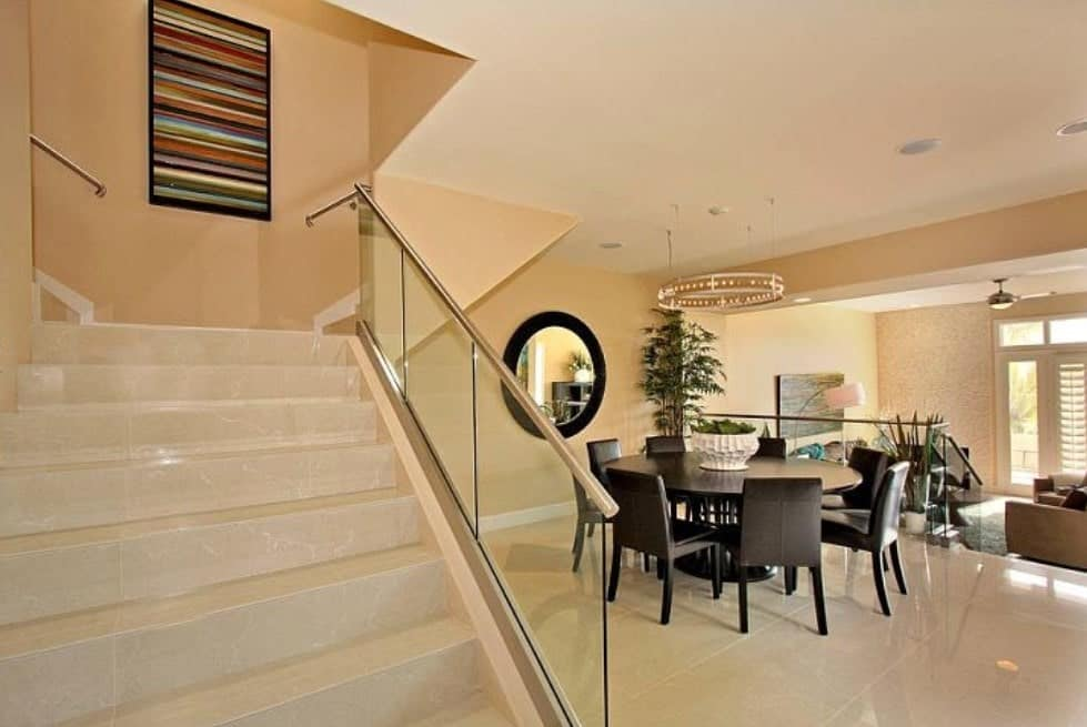 Modern home with a large staircase with classy tiles flooring and glass railings.