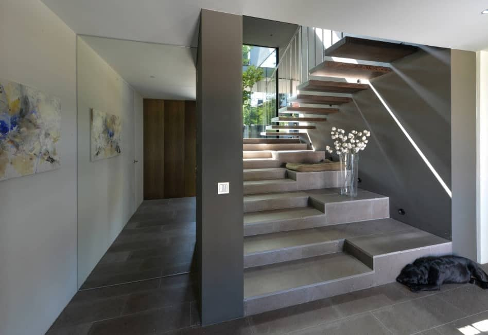 A modern home with a very stylish staircase. The large glass window lets the sunlight through, brightening the staircase area.