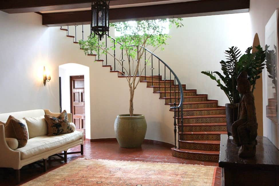 Mediterranean home featuring a curved staircase with classy red tiles flooring and white walls.