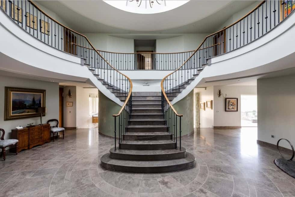 A foyer with a split-type staircase boasting stylish black tiles flooring and iron railings with gold-finished handrails.
