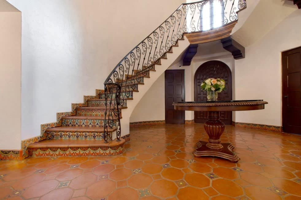 A foyer with very attractive tiles flooring and a round centerpiece table. The staircase offers classy railings.