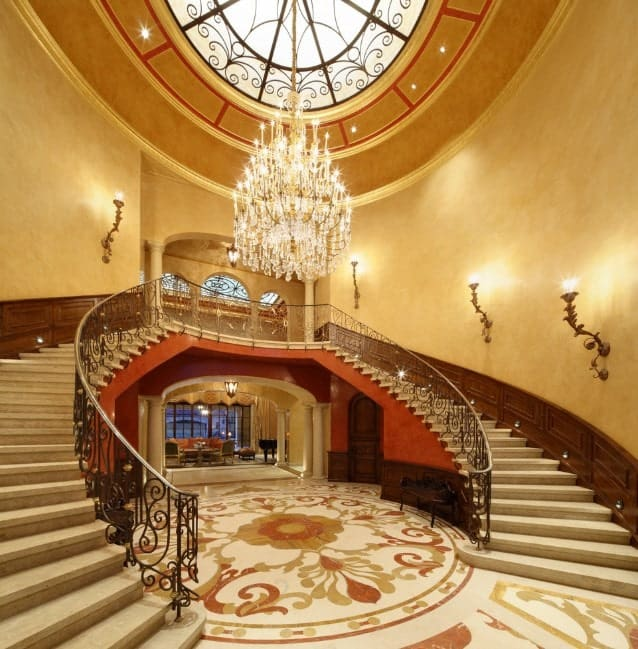 A grand foyer featuring a double staircase lighted by wall lights and a spectacular grand chandelier.