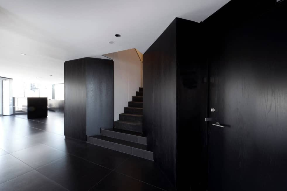 A contemporary home with black tiles flooring and black walls, along with a slim black staircase.